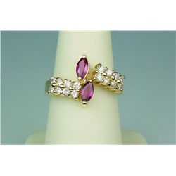 Elegant 14 karat yellow gold ladies by-pass  design ring set with two matching MQ red  rubies and 16