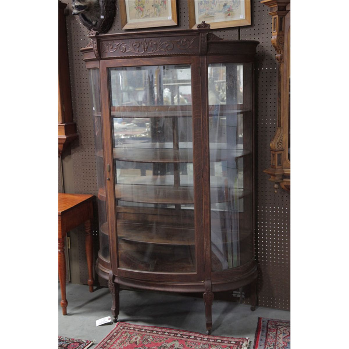 CHINA CABINET. Oak Having A Foliate Carved Crest, Curved Glass Door And  Sides And Resting On Shaped