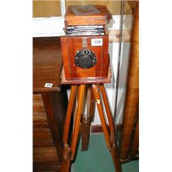 A C19th mahogany bellows camera with plates on a tripod stand with Compur shutter