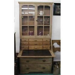 An early C20th elm drop-leaf bureau bookcase with glazed top above a drop-leaf bureau containing a g