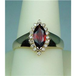Stylish 14 karat yellow gold ladies ring set  with a center MQ cut garnet weighing approx.  2.00 car