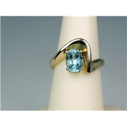 Elegant 14 karat yellow gold ladies freeform  design ring set with a center oval blue  Aquamarine we