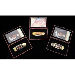 Lot of three folding pocket knives in  separate wood display cases with scales given  tribute to the
