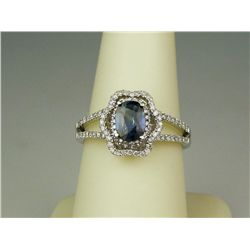 Dazzling 14 karat white gold ladies ring set  with a center oval blue sapphire weighing  approx. 1.0