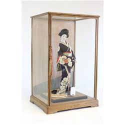 Japanese doll in glass box with wood frame