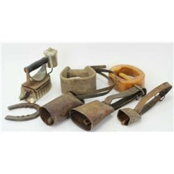 Collection of 7 antiques includes 3 cow bells with leather straps, one pair horse shoes, gas iron, s
