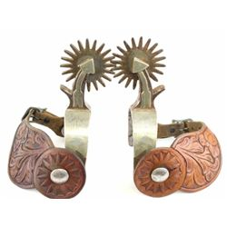 Pair Crockett marked arrow shank spurs single mounted with unmarked floral carved leather straps.