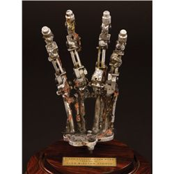 T-800 SCREEN-USED ENDOSKELETON HAND FROM TERMINATOR 2: JUDGMENT DAY ON DISPLAY BASE