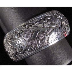2304 - TIBETAN SILVER CUFF BRACELET W/LOTUS AND OTHER OBJECTS