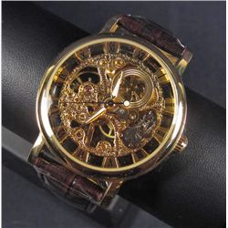 5740 - MENS GOLD TONE SKELETON WATCH W/ QUARTZ MOVEMENT AND LEATHER BAND