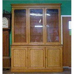 A Victorian honey oak library bookcase on cabinet the moulded cornice above a triple bookcase enc...