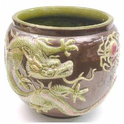A Bretby majolica glaze jardiniere, relief moulded with a 4 claw green dragon against a brown gro...