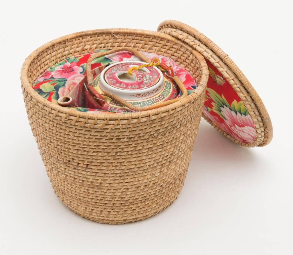 Colorful Chinese porcelain tea pot in insulated woven basket tea ...