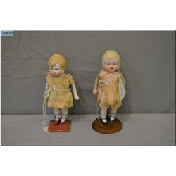 "A pair of 7"" Nippon all-bisque dolls with painted eyes, shoes and socks and hand made antique dresse"