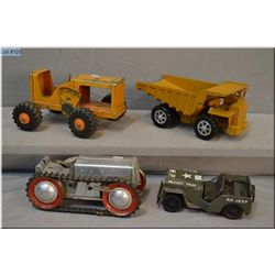 Selection of vintage toys including wind-up tractor, military jeep, Marx tractor and Ertl dump truck