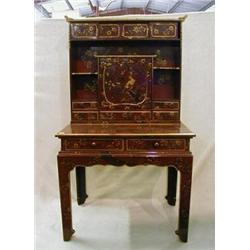 A fine quality Oriental red lacquered writing table with raised back fitted various shelves, cupb...
