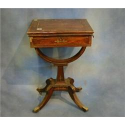 A Regency rosewood and brass inlaid games/work table, the swivel top with hinged lid revealing an...