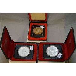 Three cased Canadian silver dollars including 1973 RCMP, and two 1975 Calgary