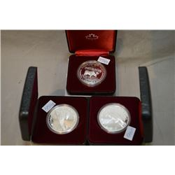Three cased Canadian silver dollars including 1984 Toronto, 1985 National Parks and 1986 Vancouver