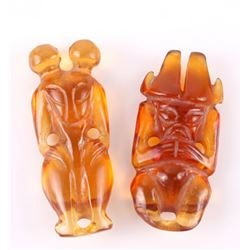 Two (2) carved amber figures in the form of a netsuke