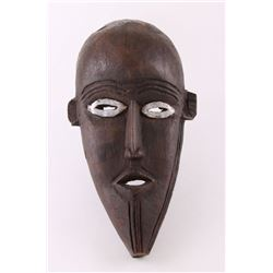 African mask carved from ebony lined with metal eyes.