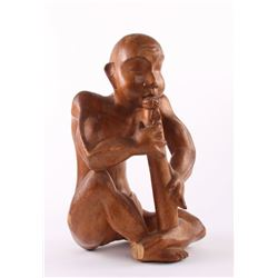 Indonesian wood sculpture carving of a man playing an
