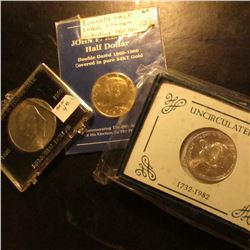 Eisenhower Dollar in broken plastic case; 1983 D Gold-plated and counterstamped Kennedy Half Dollar
