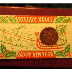 "1935 Lincoln Cent stamped with ""Greeting"" and Santa Claus, in a vintage ""Merry Xmas Happy New Year"""