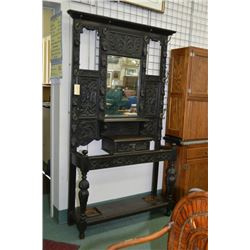 Antique heavily carved fumed oak hall stand with glove drawer, bevelled mirror, coat hooks, cane and