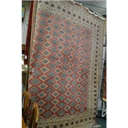 Large wool area rug with overall geometric pattern, multiple narrow borders, coral background in sha