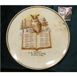 "1912 Calendar Saucer ""Compliments J.H. Dethlefs,/Ricketts, Iowa"", Owl standing on book opened to the"