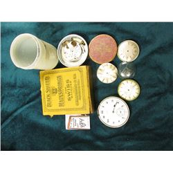 """Black Shield Mainsprings for Swiss Watches empty box; several watch movements and dials."
