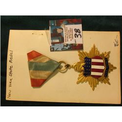 "Brass enameled Badge with Ribbon. Pendant has star burst design, shield with Liberty Cap and ""Nova Y"