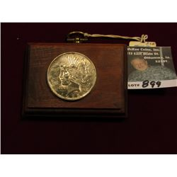 Walnut Plaque with 1922 U.S. Peace Silver Dollar attached. Toned Uncirculated.