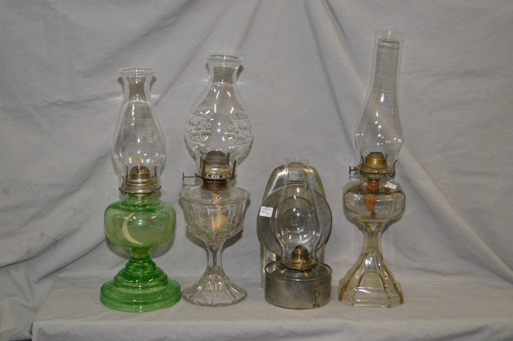 Four vintage oil lamps including English made wall mount with reflector, green glass lamp and two cl