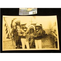 T.A. Powell, photographer of Indians, black and white Postcard of Indians holding Spear and U.S. fla