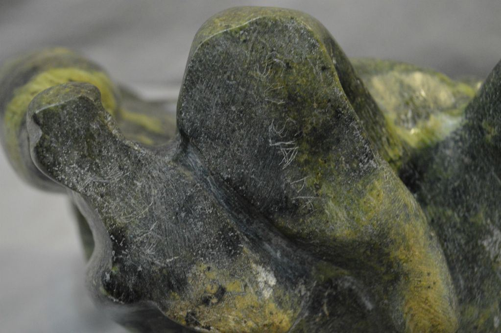 Carved soapstone of an inuit man with seals no signature
