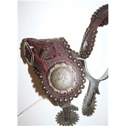 Silver inlaid spurs with large rowels, tooled  leather straps with silver engraved conchos  and bras