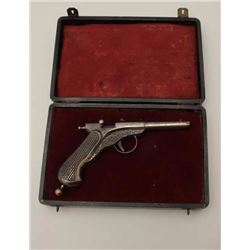 """All cast metal spring gun in case, replaced  parts, French 19th Century, approximately  8.5"""" overall"""