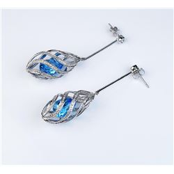 Designer drop earrings set with Swiss Blue  topaz and diamonds in 14 karat white gold  settings. Est