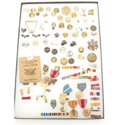 Lot of U.S. military medals and insignias in  large riker case.       Est.:  $100-$200.