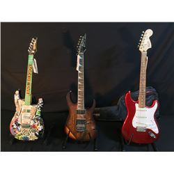 3 GUITARS: HEAVILY STICKERED STRAT STYLE GUITAR, SQUIER STRAT, AND IBANEZ RG420CM GUITAR WITH