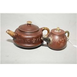Two purple clay Oriental teapots, each one with jade spout, finial and handle and both are engraved