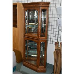 Modern oak two door corner display cabinet with glass shelves and bevelled glass doors