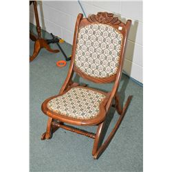 Oak framed tapestry upholstered folding nursing rocker with carved floral motif back