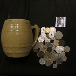 "Stoneware Mug ""Uhl Pottery Co. 16 Huntingburg Ind."" with a large group of unsorted foreign coins and"