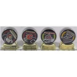 SET OF 4 NHL INCASED HOCKEY PUCKS ON STAND