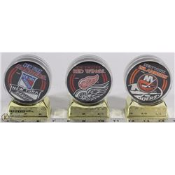 SET OF 3 NHL INCASED HOCKEY PUCKS ON STAND