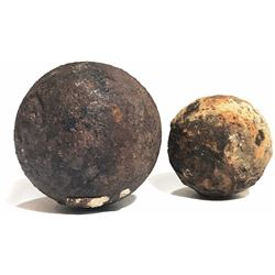 Lot of two iron cannonballs (one small and encrusted, the other broken off a barshot) from the 1733