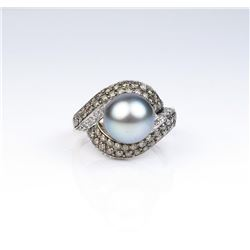 Exquisite ring featuring a center black South  Sea Pearl averaging 10.00 MM in diameter of  nice col